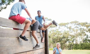 Person being helped over an assault course wall
