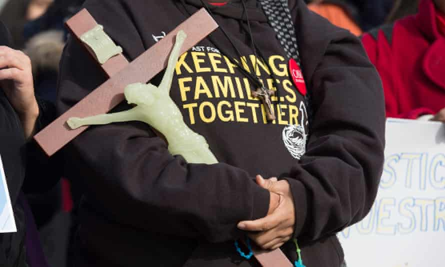 A woman holds a large crucifix during a rally held by immigration advocates outside the supreme court in Washington on 15 January 2016.