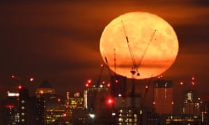 A full moon rises behind skyscrapers at UK's banking headquarters at Canary Wharf in east London.