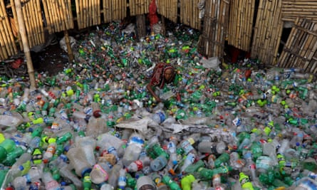 A woman works in a plastic bottle recycling factory in Dhaka, Bangladesh.
