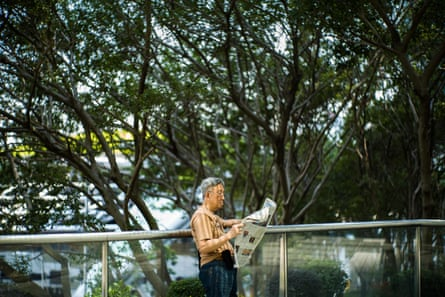 A man reads his newspaper as he stands near trees on an elevated walkway in Hong Kong.