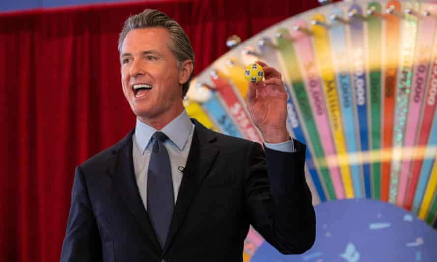 California governor Gavin Newsom holds a lottery ball selected for the first of 15 Californians to be awarded $50,000 for doing their part in getting vaccinated against Covid-19.
