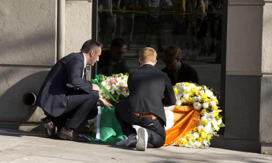 Philip Grant, Irish consul general to the western United States (left) lays an Irish flag at the scene of the balcony collapse.