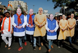Supporters of India's ruling BJP wearing cut-outs of PM Modi and the party president Amit Shah