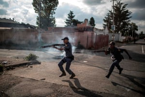 Police officers in Johannesburg fire rubber bullets as they chase residents protesting against the lack of basic necessities, such as access to water and electricity, in the working class suburb of Turffontein. Demonstrators blocked roads, burning tyres, mattresses and tree branches after allegedly unfair allocation of new social housing.
