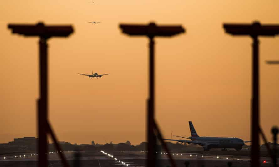Passenger aircraft prepare to land during sunrise at Heathrow airport in London.