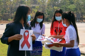 Government workers from the ethnic affairs ministry prepare red ribbons, symbols of resistance to the coup, during a strike at their headquarters in Naypyidaw