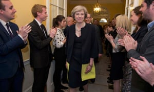 Staff applaud Theresa May, and her husband Philip, walk into 10 Downing Street.