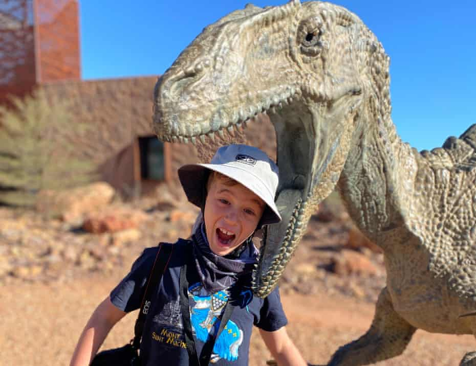 Sally Dillon's son with a dinosaur sculpture at the Australian Age of Dinosaurs museum in Winton, central Queensland