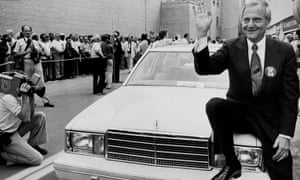 As CEO of Chrysler, Lee Iacocca sits on the hood of K Car Number One, a Plymouth Reliant, in Detroit in 1980.