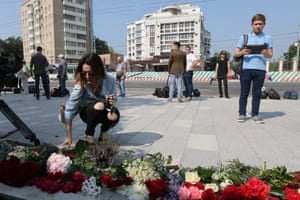 A woman lays flowers at the French Embassy in Moscow