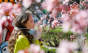 A girl removes the mask to smell the flowers on a blooming tree following the outbreak of the coronavirus disease in Skopje, North Macedonia 20 March, 2020.