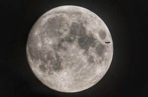Northumberland, England: A plane passes across the face of the moon as it rises over the north-east