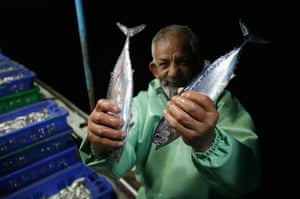 Abu Issam, who has been a fisherman for 50 years, shows off his catch