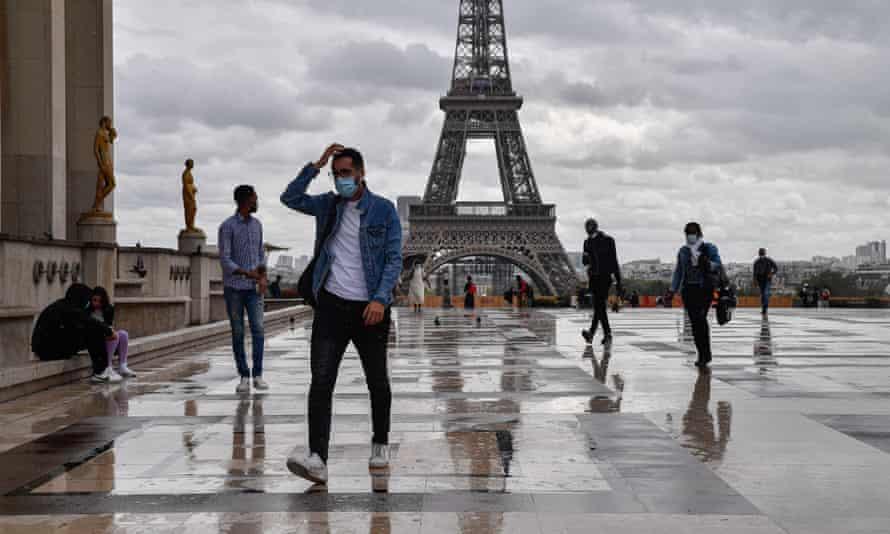 People wear medical masks near the Eiffel Tower in Paris, France