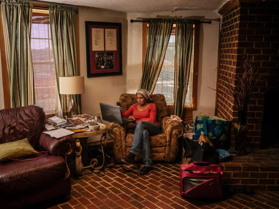 Kara Brewer Boyd works in the living room of their home in Baskerville, Virginia. 'Some days I don't leave this chair,' said Boyd, the event and program coordinator for the National Black Farmer's Association founded by John.