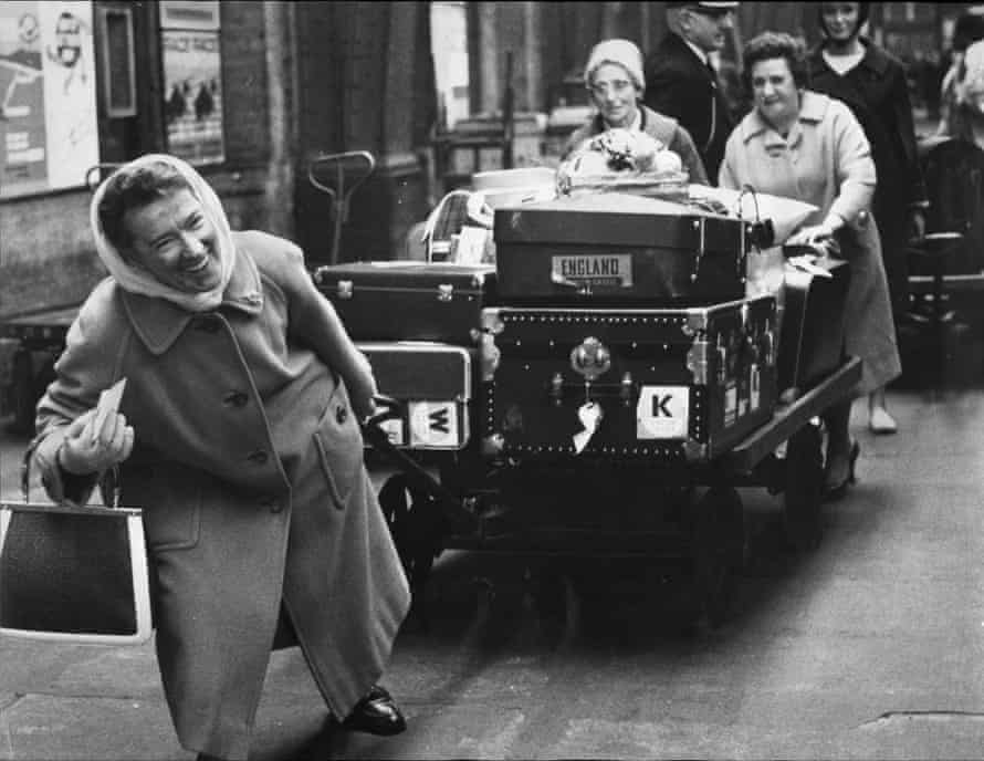 An archive photograph of women pulling along their own luggage at London's St Pancras train station during a porter strike.