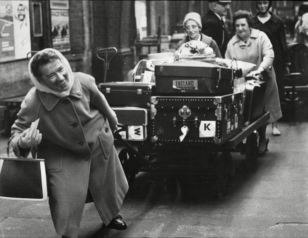Foto van vrouwen die kar met koffers trekken