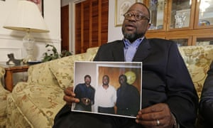 Anthony Scott, Walter's brother, holds a photo of himself, center, Walter, left, and his other brother Rodney, right.