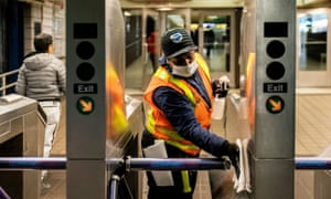 An MTA worker cleans turnstiles at the Times Square subway station.