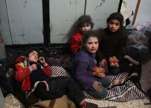 Children wait at a makeshift hospital