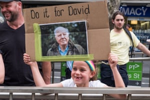 A young protester holding a placard reading 'Do it for David' with a picture of broadcaster David Attenborough
