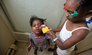Promise Ward, six, right, washes her two-year-old sister Sharell's face using tap water.