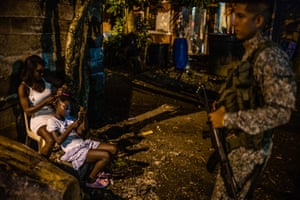 As a soldier patrols, a young woman combs the hair of a child on a street in Buenaventura