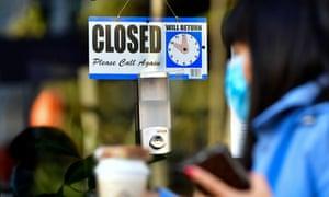 Seorang wanita berjalan melewati tanda tertutup yang tergantung di pintu sebuah bisnis kecil di Los Angeles