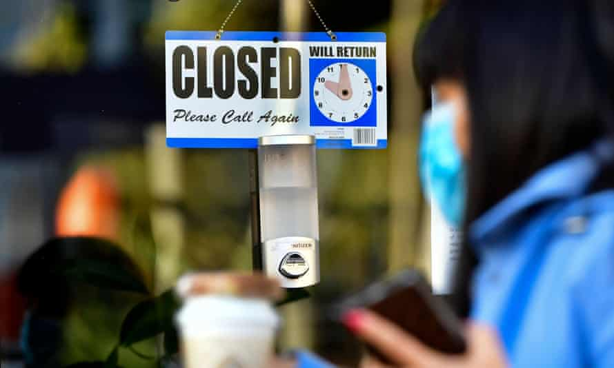 Woman walks past a closed sign hanging on the door of a small business in Los Angeles
