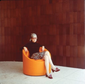 Gere Kavanaugh in an orange tub chair made from a Sonotube against brown tiled wall.