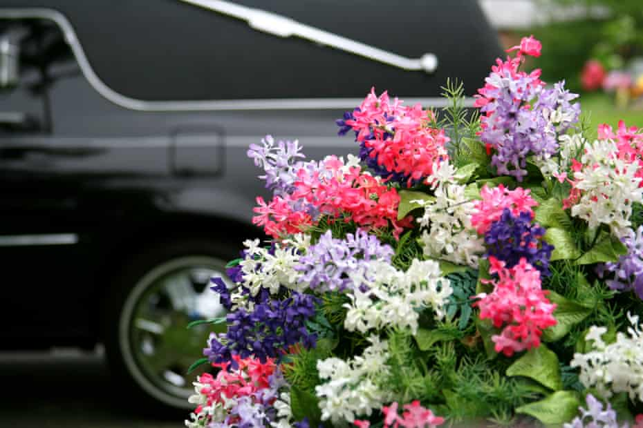 Flowers in front of a black hearse.