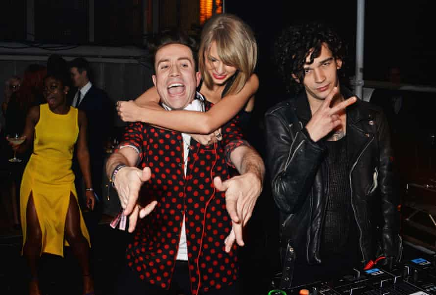 Matt Healy of band the 1975 with singer Taylor Swift and DJ Nick Grimshaw at the 2015 Brits party