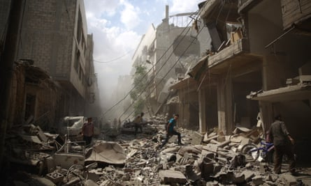 Syrians walk amid the rubble of destroyed buildings following reported airstrikes by regime forces in the rebel-held area of Douma, east of the capital Damascus.