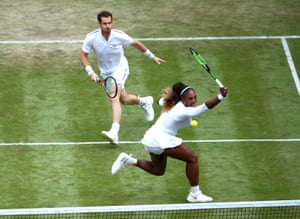 Serena Williams plays a backhand returns at the net as her partner Andy Murray looks on.
