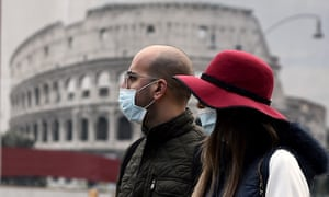 A couple wearing face masks walk past a poster representing the Colosseum amid the Covid-19 pandemic in central Rome.