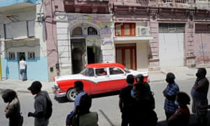 A vintage car passes by people who line up to buy food amid concerns about the spread of coronavirus in Havana, Cuba.