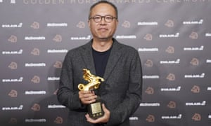 Taiwanese director Chung Mong-hong holds his award for best director for the film A Sun.