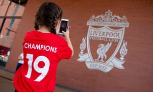 Euphoric Liverpool fans continue jubilations after clinching first league title in 30 years<br>epa08510738 A young Liverpool FC supporter takes a picture of her team's crest while celebrating outside Anfield stadium in Liverpool, Britain, 26 June 2020. Liverpool have been crowned champions of the Premier League for the first time in three decades after Chelsea FC beat Manchester City FC 2-1 on the night of 25 June. Man City's failure to win this crucial duel mathematically handed the English top league title to the Liverpudlian club led by German manager Juergen Klopp.  EPA/PETER POWELL .