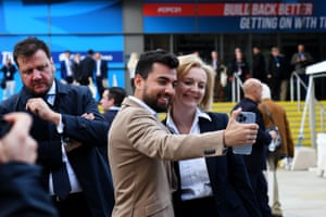 Liz Truss posing for a selfie with a man outside the conference hall.