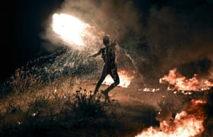 A Palestinian protester burns tyres during a demonstration along the border between Israel and Gaza.