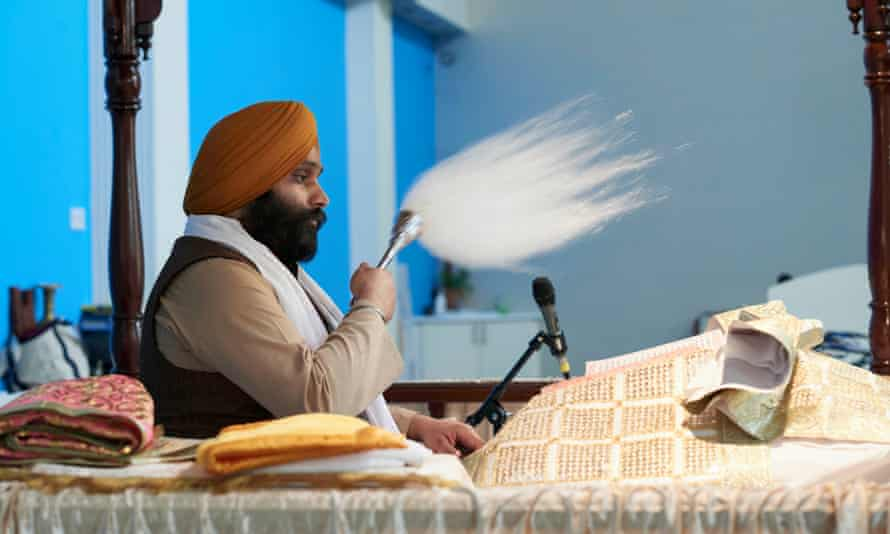 The sitting granthi reverently fans the scripture of the Guru Granth Sahib at Ramgarhia Sikh gurdwara