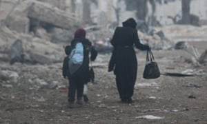 A woman and children leave an area of eastern Aleppo after bombardment by government forces.