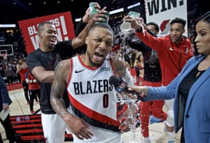Portland's Damian Lillard has water poured on him by teammates Rodney Hood, left, and guard Evan Turner (right) after game five.
