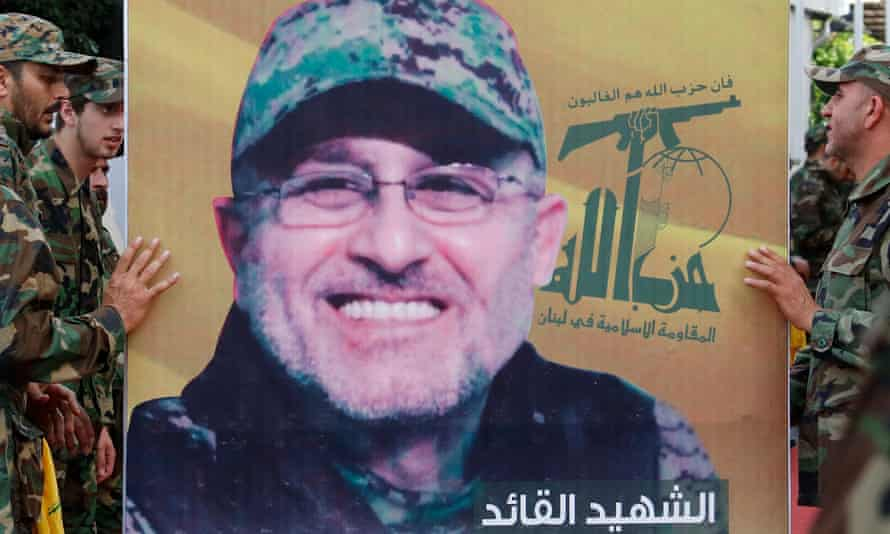 Hezbollah members hold a picture of Badreddine during his funeral.