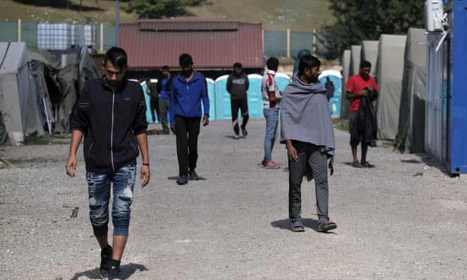 Migrants walk through the Lipa camp, outside Bihać, Bosnia