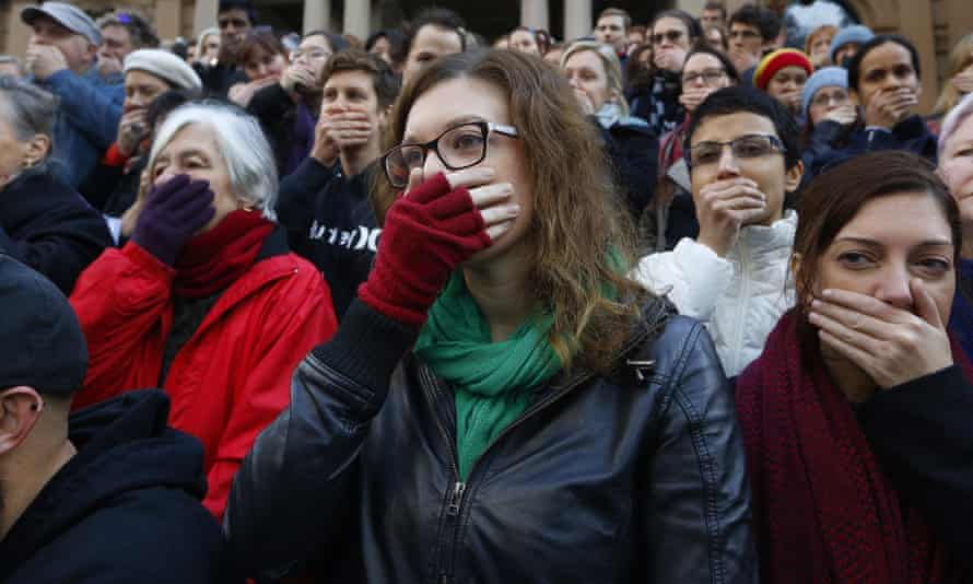 Supporters cover their mouths during a protest by doctors and allied health professionals in Sydney to oppose the secrecy provisions of the Border Force Act, in July 2015.