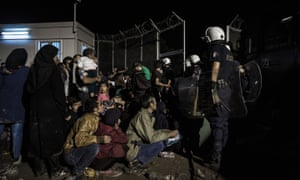A registration camp on the Island of Lesvos at nightfall, with a group of refugees tired and frustrated sitting in the cold waiting to be processed, armed police standing over them