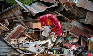A man looks for his belongings amid the debris of his destroyed house in Palu.