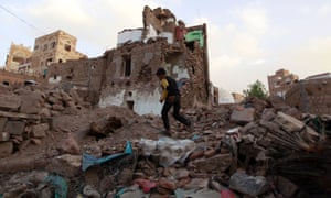 A Yemeni boy runs past buildings damaged by air strikes